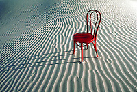 Red chair in sand dunes.
