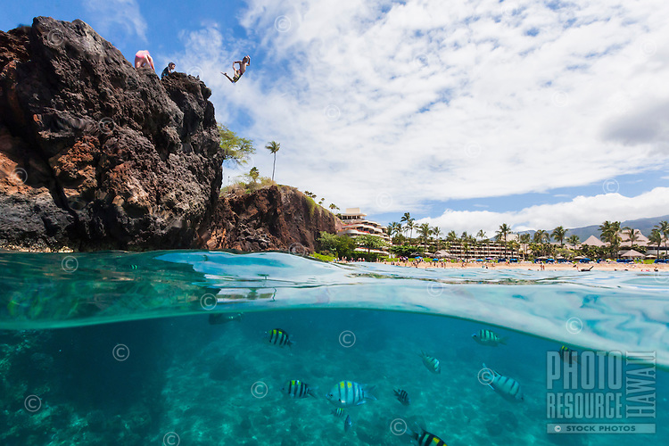 Split-level view of kids cliff jumping into the ocean with a view of hotels and people sunbathing in the background, Maui.