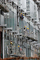 Workers place the curtain wall of a commercial complex in Beijing, China..