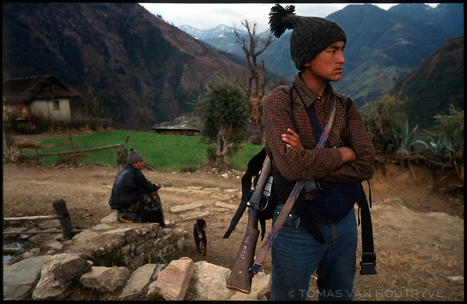 An armed Maoist rebel soldier of the People's Liberation Army waits for other rebels to arrive in the village of Mahat, Nepal on Tuesday, 22 February 2005.<br />