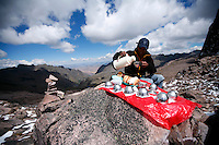 A porter pours coca tea atop Pachachutec Pass in the Lares Valley, on May 16, 2008. The Lares Valley contains crystal-clear lakes and unspoiled mountain vistas, the network of valleys is also populated by the Quechua, indigenous Inca people of Southern Peru with their small villages dotting the region.