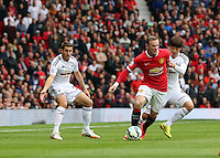 Pictured: Wayne Rooney of Manchester United (C) is challenged by Ki Sung Yueng (R), Angel Rangel (L) looks on. Saturday 16 August 2014<br />