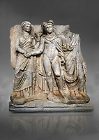 "Roman Sebasteion releif sculpture of emperor Claudius and Agrippina, Aphrodisias Museum, Aphrodisias, Turkey.  Against a grey background.<br /> <br /> Claudius in heroic nudity and military cloak shakes hands with his wife Agrippina and is crowned by the Roman people or the Senate wearing a toga. The subject is imperial concord with the traditional Roman state. Agrippina holds ears of wheat: like Demeter goddess of fertility. The emperor is crowned with an oak wreath, the Corona civica or ""citizen crow"", awarded to Roman leaders for saving citizens lives: the emperor id therefore represented as saviour of the people."