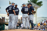New York Yankees manager Joe Girardi (28) talks with third baseman Chase Headley (12) during a pitching change as shortstop Jorge Mateo (hidden), second baseman Starlin Castro (14), first baseman Greg Bird (33), and catcher Austin Romine (27) listen in during a Grapefruit League Spring Training game against the Pittsburgh Pirates on March 6, 2017 at LECOM Park in Bradenton, Florida.  Pittsburgh defeated New York 13-1.  (Mike Janes/Four Seam Images)