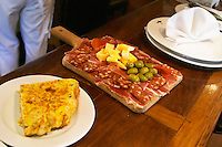 Bar food: omelette on a white plate and a wooden cutting board with charcuteries, spicy sausages, olives cheese, dry cured ham, in the restaurant El Palenque, the sword fish swordfish, in the Mercado del Puerto, the market in the port harbour harbor where many people go and eat and shop on weekends Montevideo, Uruguay, South America