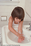 3 year old girl washing hands in sink self care vertical