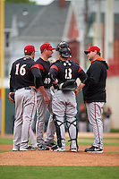 Richmond Flying Squirrels pitching coach Steve Kline (right) talks with Kyle Crick (49) as Jackson Williams (8) and Myles Schroder (16) listen in during a game against the Erie Seawolves on May 19, 2015 at Jerry Uht Park in Erie, Pennsylvania.  Richmond defeated Erie 8-5.  (Mike Janes/Four Seam Images)