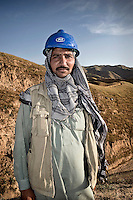A foreman wearing a keffiyeh and a hard hat standing in the hills.