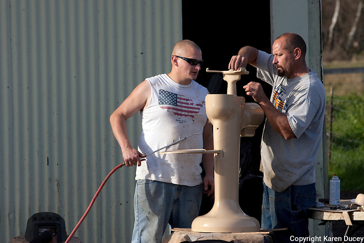 """Anthony Estrella, right, gets help from Mark Outland while restoring a cream separator at Tthe Estrella Family Creamery in Montesano,Wash.  on November 4, 2010.  """"We're just trying to live the dream"""" says Anthony. """"You can see we're not exactly getting filthy rich off this.""""  The Food and Drug Administration ordered the Estrella Family Creamery in Montesano,Wash.  to stop processing cheeses after it found listeria bacteria on some of the cheeses this year.  The family says they have made many renovations on the farm and the bacteria is only found on the soft cheese, not everything.  They believe they should be allowed to resume making cheese and sell the hard cheeses they have already made at the facility.  The creamery is one of Washington's most famous artisan cheesemakers.  (photo credit Karen Ducey). ."""