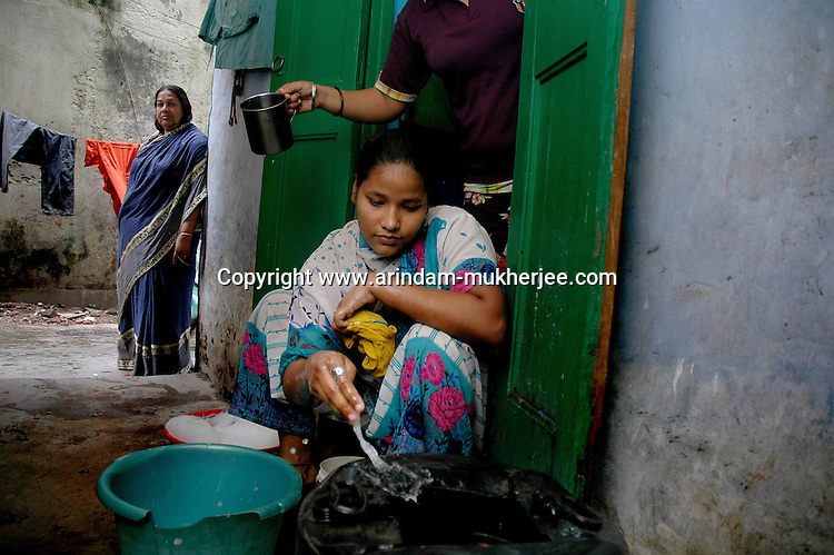 INDIA (West Bengal - Calcutta)July 2007, Sanno Babe  washing clothes while her mother Banno Begum watches her at their  small two roomed apartment in Iqbalpur.  10 family members share this apartment.   Shakila and Shanno are twins from a poor muslim family of Iqbalpur, Kolkata. . Inspite of their late father's unwillingness to send his daughters to take up  boxing her mother Banno Begum inspired them to take up boxing at the age of 3. Their father was more concerned about the social stigma they have in their community regarding women coming into sports or doing anything which may show disrespect to the religious emotions of his community. Shakila now has been recognised as one of the best young woman boxers of the country after she won the  international championship at Turkey in the junior category. Shanno is also been called for the National camp this year. Presently Shakila and shanno has become the role model in the Iqbalpur area  and parents from muslim community of Iqbalpur have started showing interst in boxing. Iqbalpur is a poor muslim dominated area mostly covered with shanty town with all odds which comes along with poverty and lack of education. - Arindam Mukherjee
