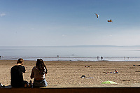 Pictured: People enjoy the sunshine on the beach in Barry Island. Tuesday 20 April 2020<br /> Re: Pre-election campaign in the Vale of Glamorgan, Wales, UK.