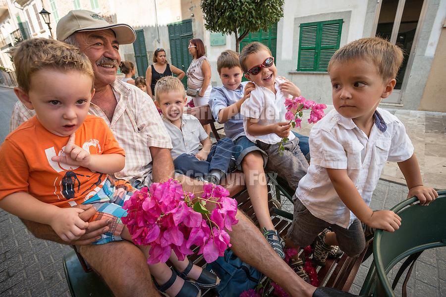A man with several young boys drives his horse-drawn carts in a street parade, during the fiesta: Mare de Déu de la Salut, Sant Lloranc, Mallorca