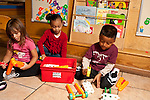 Education preschool 3-4 year olds two girls and a boy playing side by side but separately with colorul plastic construction toy