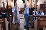 St Walstans Day, Bawburgh, St Mary and Saint Walstan's Church Norfolk 2018. Church members gather for Sunday church service and then process to the Holy healing well not far away.  <br /> <br /> Bishop Tony Foottit says a few words and then presents long standing Church Warden Stan ?? with gifts from the congregation for services to the church community.<br /> <br /> St Walstan dedicated his life to farming and the care of farm animals, he is the patron saint of saint of farm workers, farmers and farm animals. He died 30 May 1016, while at work in a meadow.