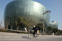 A cyclist rides past the newly completed Oriental Arts Center in Pudong Shanghai, China. Designed by French Architect Paul Andreau, the center will host a variety of large concerts and performances..08-JAN-05