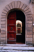 A detail of a doorway within a doorway, looking into a courtyard in Florence, Italy.