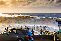Spectators watch giant waves crest and crash against rocks during a large winter swell at Shark's Cove, North Shore, O'ahu.