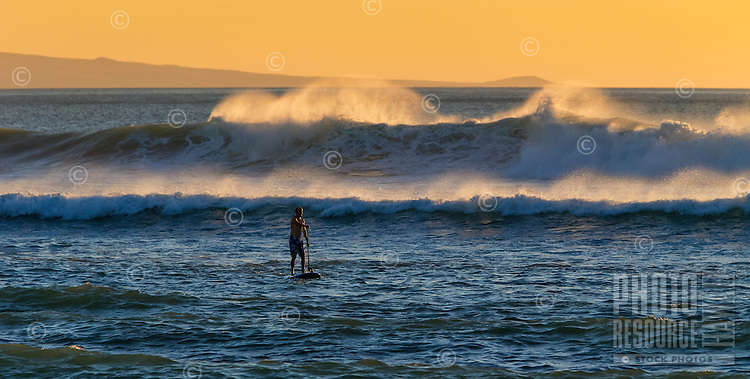Stand up paddler enjoys some big waves and the sunset at Kawaihae on the Big Island.