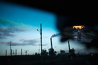 A thermoelectric plant is seen through the window of a car while a cyclist is seen the the rear view mirror in Cienfuegos, Cuba on 5 March 2009.