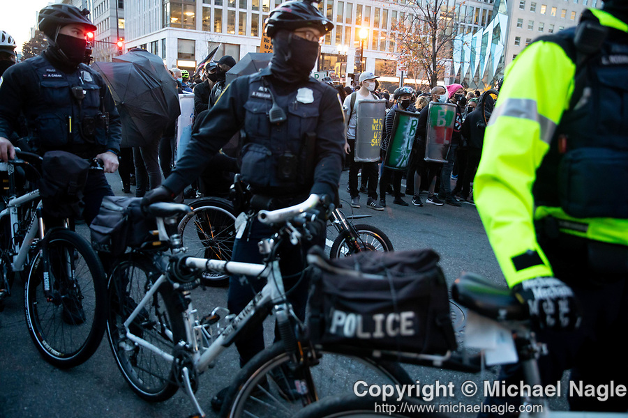 """DC police break up clashes between pro-Trump and anti-Trump demonstrators near Black Lives Matter Plaza during the """"Million MAGA March"""" on November 14, 2020 in Washington, D.C.  Thousands of supporters of U.S. President Donald Trump gathered to protest the results of the 2020 presidential election won by President-Elect Joe Biden.  Photograph by Michael Nagle"""