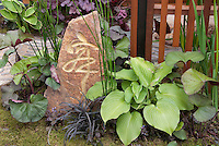Japanese calligraphy ornament on garden stone, with Equisetum, Hosta, Heuchera in Asian theme Oriental garden