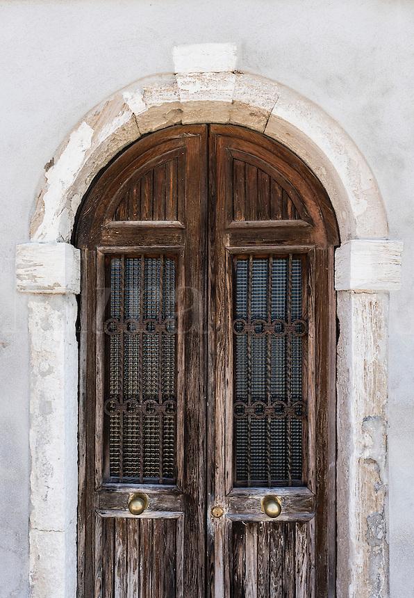Rustic arched wooden door,  Murano, Venice, Italy