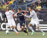 New England Revolution midfielder Kelyn Rowe (11) dribbles as Real Salt Lake defender Carlos Salcedo (16) pressures. In a Major League Soccer (MLS) match, Real Salt Lake (white)defeated the New England Revolution (blue), 2-1, at Gillette Stadium on May 8, 2013.