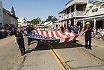 The Ione Fire Department carries a large U.S. flag during the annual Ione Homecoming Parade on Main Street, Amador Country, Calif.