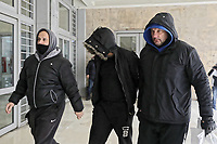 Pictured: The unnamed PAOK supporter (C) believed to the the one who threw n object, is led to the Public Prosecutor in Thesaloniki, Greece. Monday 26 February 2018<br /> Re: Sunday's Greek Super League derby between PAOK Thessaloniki and Olympiakos was called off after Olympiakos' manager Oscar Garcia was struck in the face by an object believed to be a till machine paper roll, thrown by a spectator minutes before kick-off.<br /> Garcia left Toumba Stadium for a local hospital to seek treatment for a bloodied lip.<br /> The incident prompted the Olympiakos team to leave the pitch in protest before riots erupted outside the ground.<br /> Angry PAOK fans leaving the stadium then clashed with police who used tear gas to quell the violence.