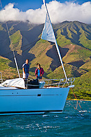 Couple on bow of cruising sailboat at anchor in Kamalo Harbor off Molokai, Hawaii