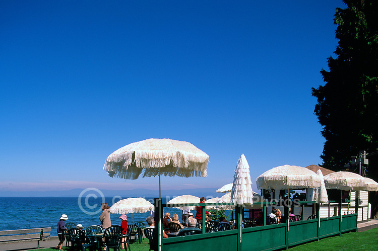 """People eating and drinking at an Outdoor Sidewalk Cafe along the Waterfront of Qualicum Beach, in the """"Oceanside Region"""" of Vancouver Island, British Columbia, Canada"""