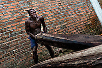 A Colombian sawmill worker lifts a heavy timber from the Pacific rainforest in Tumaco, Colombia, 18 June 2010. Tens of sawmills located on the banks of the Pacific jungle rivers generate almost half of the Colombia's wood production. The wood species processed here (sajo, machare, roble, guabo, cargadero y pacora) are mostly used in the construction industry and the paper production. Although the Pacific lush rainforest in Colombia is one of the most biodiverse area of the world, the region suffers an extensive deforestation due to the uncontrolled logging in the last years.