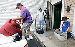 """Walter Blakesley (L) loads up the truck while his father, Buddy (L), holds onto his oxygen tank and son Andrew, 11 years-old, takes care of the family cat """"Alley"""" as their family finishes packing up their belonging on Iberville St In New Orleans to evacuate to """"points north"""" ahead of Hurricane Gustav August 31, 2008.    (Mark Wallheiser/TallahasseeStock.com)"""