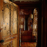 The open door leading into the hallway is hand-painted with delicate birds and flowers and adorned with fretwork like the walls