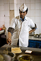 A worker making a dosa on the hotplate in the kitchen of the Indian coffee house, Baba Kharak Singh Marg. The coffee house dates back almost fifty years, first in central Connaught Place, then Janpath and now at the top of a rather shabby shopping centre. Where it is still run by the Indian Coffee Workers Cooperative Society. Once a regular haunt for politicos in Delhi, its clientele is still renowned for being well-read and intellectual.