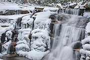 Franconia Notch State Park - Stairs Falls in the White Mountains, New Hampshire covered in snow and ice. This waterfall resembles stairs and is located along the Falling Waters Trail.