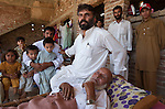 13 May 2009, Buner District , Pakistan;    Refugees from the conflict in Buner, Pakistan, Mohammad Salim (centre)  with his ailing father Pardis Khan (at right on charpoy), six brothers ,wives (hidden in room covered with kids holding up a sheet) and extended family are taking refuge in stables in the village of Bakar near Swabi. Numbering in the 70's they are sleeping up to 10 in a room after  the family  fled their home whilst the Pakistan Army attack Taliban insurgents across the Swat Valley.