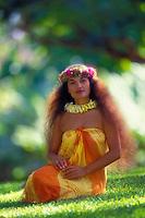 Beautiful Polynesian woman with traditional waist-length hair sitting on grass wearing an orange and yellow pareo, plumeria lei and traditional haku-lei floral headband.