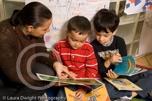 Preschool New York City ages 4-5 female parent volunteer working with two boys reading book horizontal