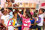 Education Preschool girls playing together in family area wearing dressup and playing with puppet interacting