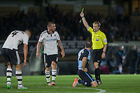 Jamie O'Hara (2nd left) of Fulham is given a yellow card by referee Gavin Ward for a foul on Garry Thompson of Wycombe Wanderers during the Capital One Cup match between Wycombe Wanderers and Fulham at Adams Park, High Wycombe, England on 11 August 2015. Photo by Andy Rowland.