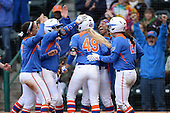Florida Gators first baseman Taylor Schwarz (49) celebrates with teammates including Kelsey Stewart (7), Alyssa Bache (8), and Bailey Castro (21) after hitting a home run during a game against the Michigan Wolverines on February 8, 2014 at the USF Softball Stadium in Tampa, Florida.  Florida defeated Michigan 9-4 in extra innings.  (Copyright Mike Janes Photography)