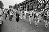 1981: the Dominica Carnival and Arts Group walks across the railway bridge at the top of Ladbroke Grove during the Notting Hill Carnival.