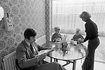 1970s England, a middle income professional couple at home with their two children. In the kitchen, mother making afternoon tea, sandwiches for the two boys, and a cup of tea for her husband who is reading the newspaper and paying no attention at all or interest in his children. 1977 New town modern housing development UK  Milton Keynes Buckinghamshire.