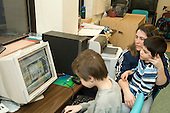 MR / Albany, NY.Langan School at Center for Disability Services .Ungraded private school which serves individuals with multiple disabilities.Parent visiting classroom  points to computer for her son to watch while another student does schoolwork on the computer. The parent is trying to help her son improve his ability to pay attention as well as helping him interact with his friend. Boy in stripes: 8, cerebral palsy, spastic quadriplegic, nonverbal with expressive and receptive language delays; Boy on computer: 10, Duchenne muscular dystrophy, expressive and receptive language delays.MR: Bud2; Hac2; Ble1.© Ellen B. Senisi