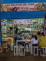 Peru, Cusco.  San Pedro Market.  Quechua Family Enjoying Ice Cream at a Stand.