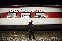 Switzerland. Canton Ticino. Lugano. Railway station. A police officer from TPO (Transport Police). The policewoman wears the special riot police black uniforms and helmet. She stand on a track and controls that none supporters from FC Luzern football club get out of the chartered train before its departure. An Intercity train with a wagon-restaurant is stopped at the station. TPO (Transport Police) is the Swiss Federal Railways Police. Swiss Federal Railways (German: Schweizerische Bundesbahnen (SBB), French: Chemins de fer fédéraux suisses (CFF), Italian: Ferrovie federali svizzere (FFS)) is the national railway company of Switzerland. It is usually referred to by the initials of its German, French and Italian names, as SBB CFF FFS. 2.06.2017 © 2017 Didier Ruef