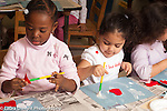 Preschool classroom 3-4 year olds art activity gluing felt hearts one girl gluing with brush held in right hand the other using her left hand