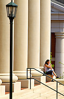 Photography of Charlotte NC's University of North Carolina at Charlotte campus (UNC Charlotte). UNCC, a public university located in northeast Charlotte, is part of the University of North Carolina higher education system. Opened in 1946, the campus has experienced explosive growth in recent years, including the addition of its Charlotte Research Institute campus and a football team. Photo shows student sitting in front of the Bioinformatics Research Center building.
