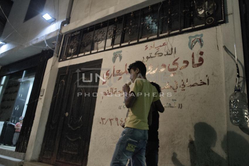 couple walkig the streets of Shatila at night. Beirut, Lebanon. August 2015